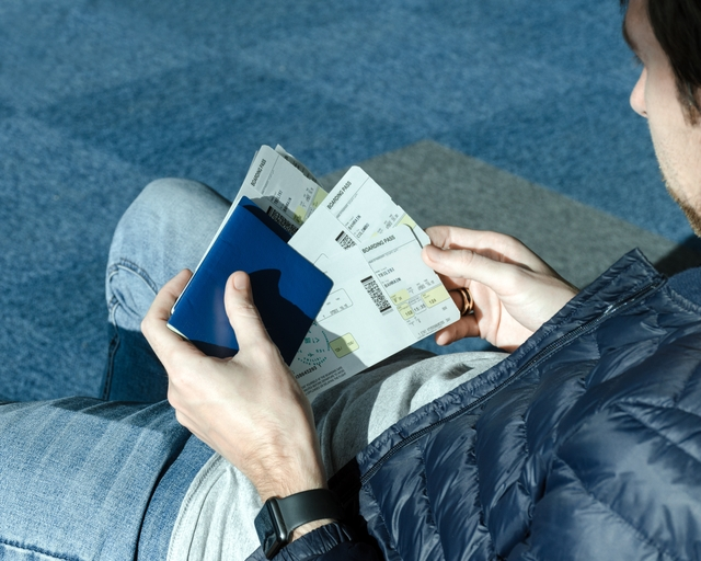 holding in hands airplane tickets and passport.