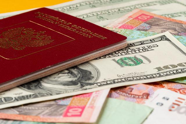 Russian passport on heap of money